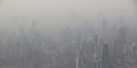 Houses and buildings are covered with haze in Shanghai, China, Wednesday, Dec. 4, 2013. China, one of the most visited countries in the world, has seen sharply fewer tourists this year - with worsening air pollution partly to blame. (AP Photo/Eugene Hoshiko)