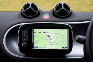 The GPS is a commonly used navigational tool. Shown is a device being used in a vehicle beside the driving wheel.
