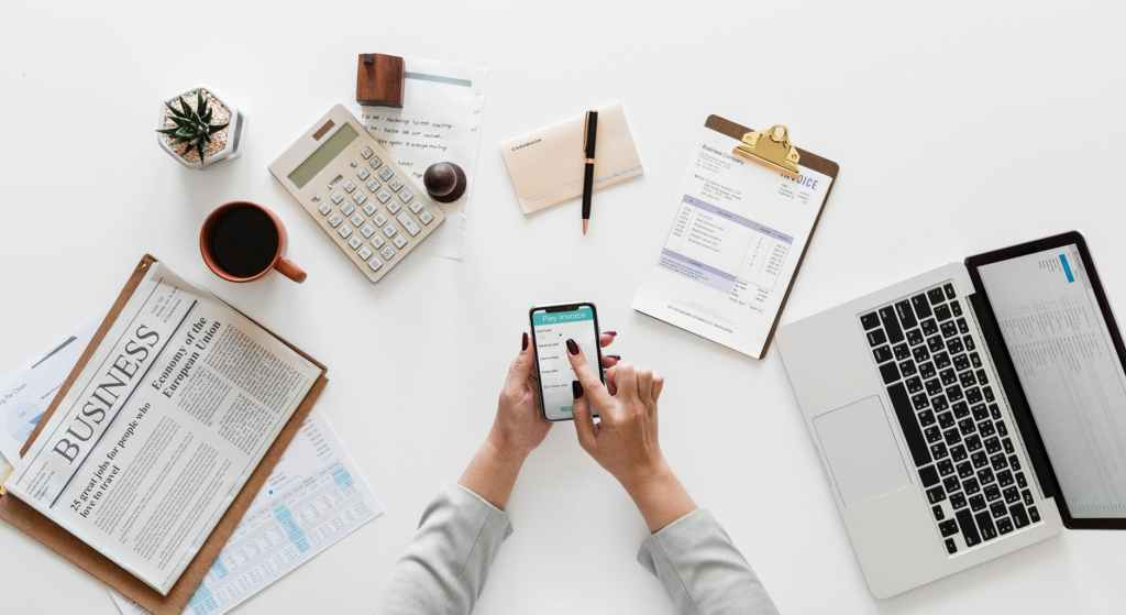 woman holding her smartphone over a desk with her laptop, a newspaper open to the Business page, a Digital Marketing Agency invoice, a checkbook, and a calculator.