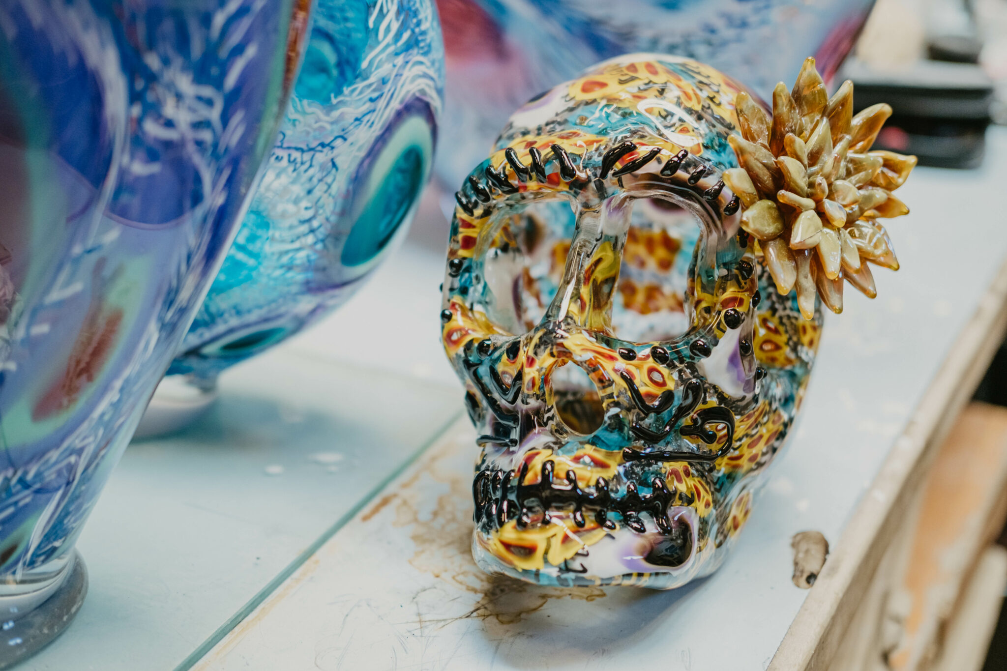A glass piece representative of a cranium with a flower attached to the left side of its head. It has a painterly feel, with teal, yellow and orange all over patterns, and dark hash marks around the eyes and mouth. This piece is much smaller in scale than the pieces surrounding it that can be seen in the edges of the frame.