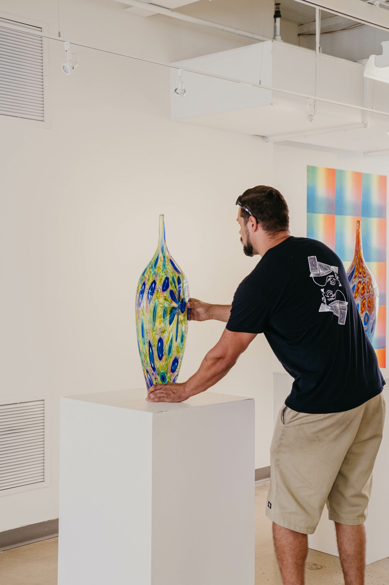 Dan Alexander, placing a tall, narrow piece of glass artwork on a white pedestal. He is turned away from the camera. The artwork is translucent blue and green.