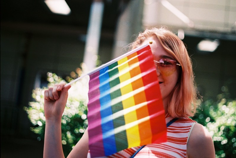 woman holding LGBT flag