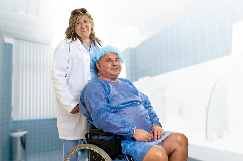Large male patient in a wheelchair with doctor