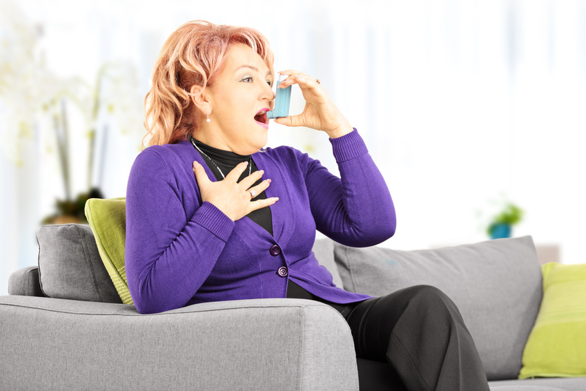 Mature woman on a sofa taking asthma treatment with inhaler