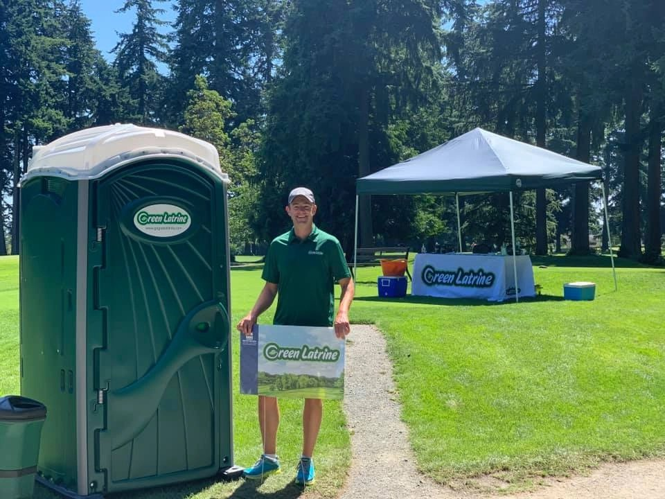 Will Niccols is standing next to the Green Latrine that we sponsored for a golf tournament with a Green Latrine Tent in the background