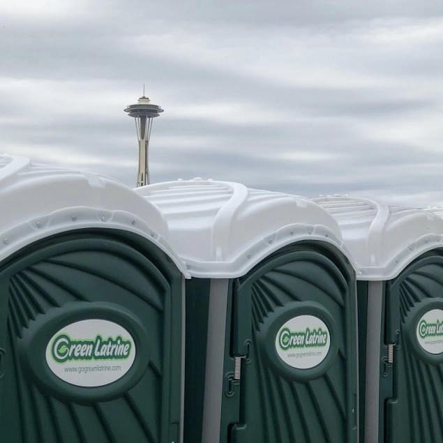 A line of Green Latrines with the space needle in the background on a classically gray Seattle day