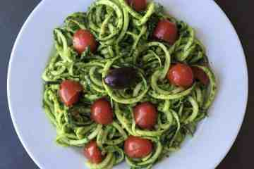 zucchini noodles with pesto and cherry tomatoes on a white plate