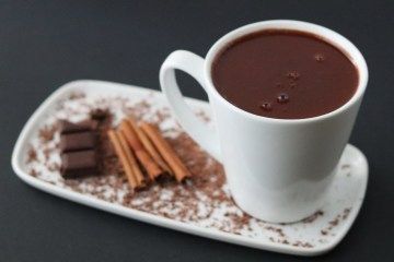 hot chocolate in a white mug on a white dish with a chocolate bar and cinnamon sticks
