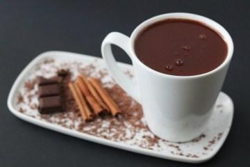 Chocolat chaud à l'ancienne dans un mug blanc sur un plat blanc avec un morceau de chocolat et des bâtons de cannelle