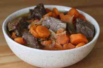 Beef stew and carrots in a white bowl