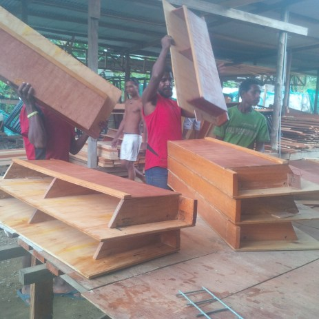 Workers packing desks for dispatch - Lae