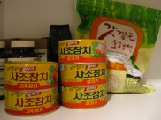 Cans of spicy tuna and bag of white rice.