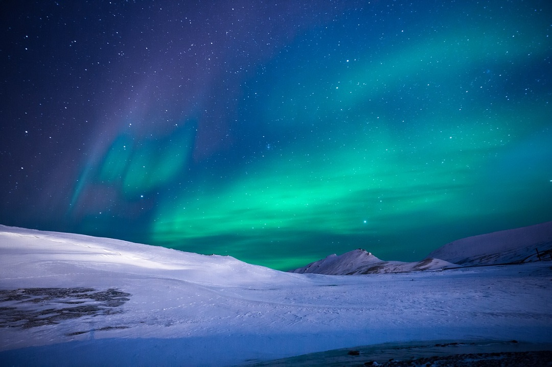 Green aurora above snowy rolling hills