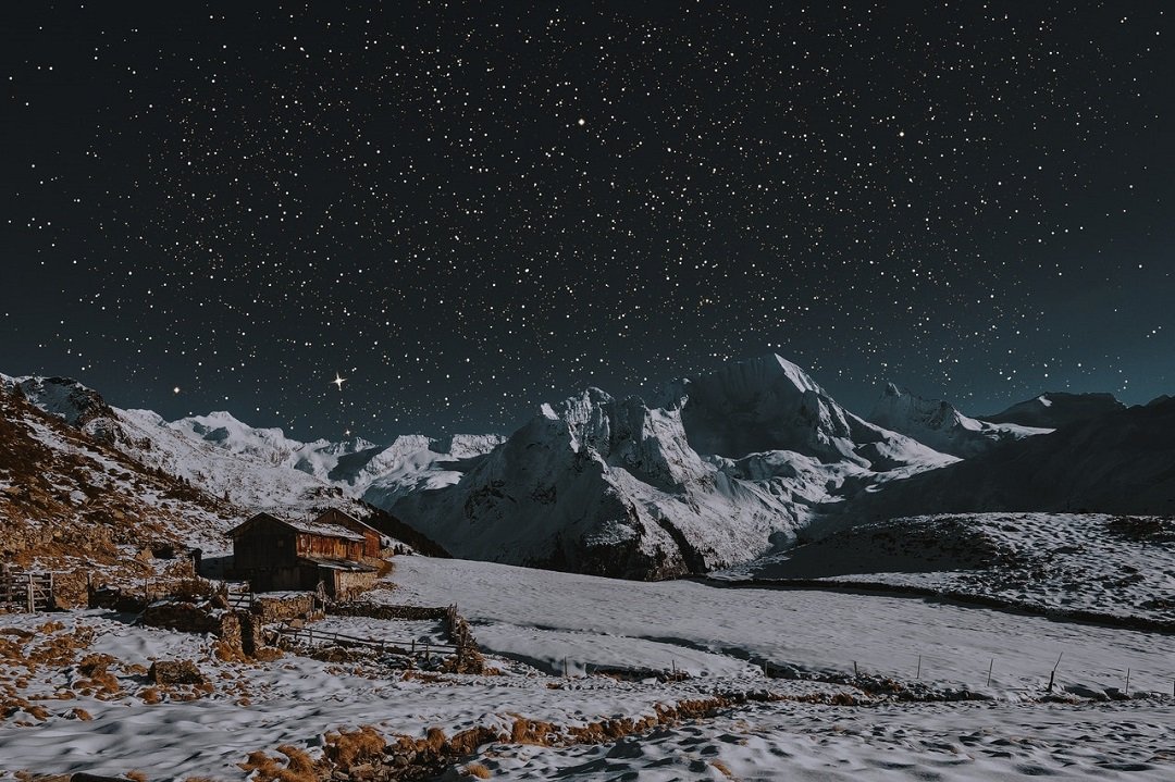 An isolated barn set against a backdrop of frozen mountains and sparkling stars