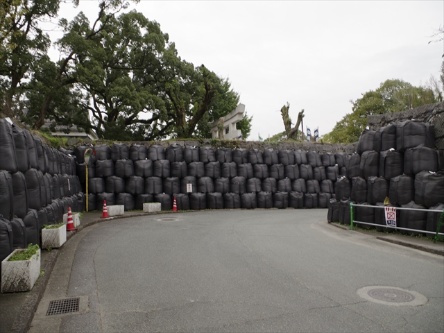A path to a Shinto shrine next to castle keeps, protected with piles of sandbags from wall collapse