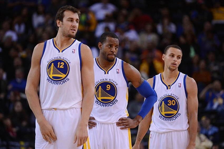 October 24, 2013; Oakland, CA, USA; Golden State Warriors center Andrew Bogut (12), shooting guard Andre Iguodala (9), and point guard Stephen Curry (30) look on during the fourth quarter against the Portland Trail Blazers at Oracle Arena. The Trail Blazers defeated the Warriors 90-74. Mandatory Credit: Kyle Terada-USA TODAY Sports