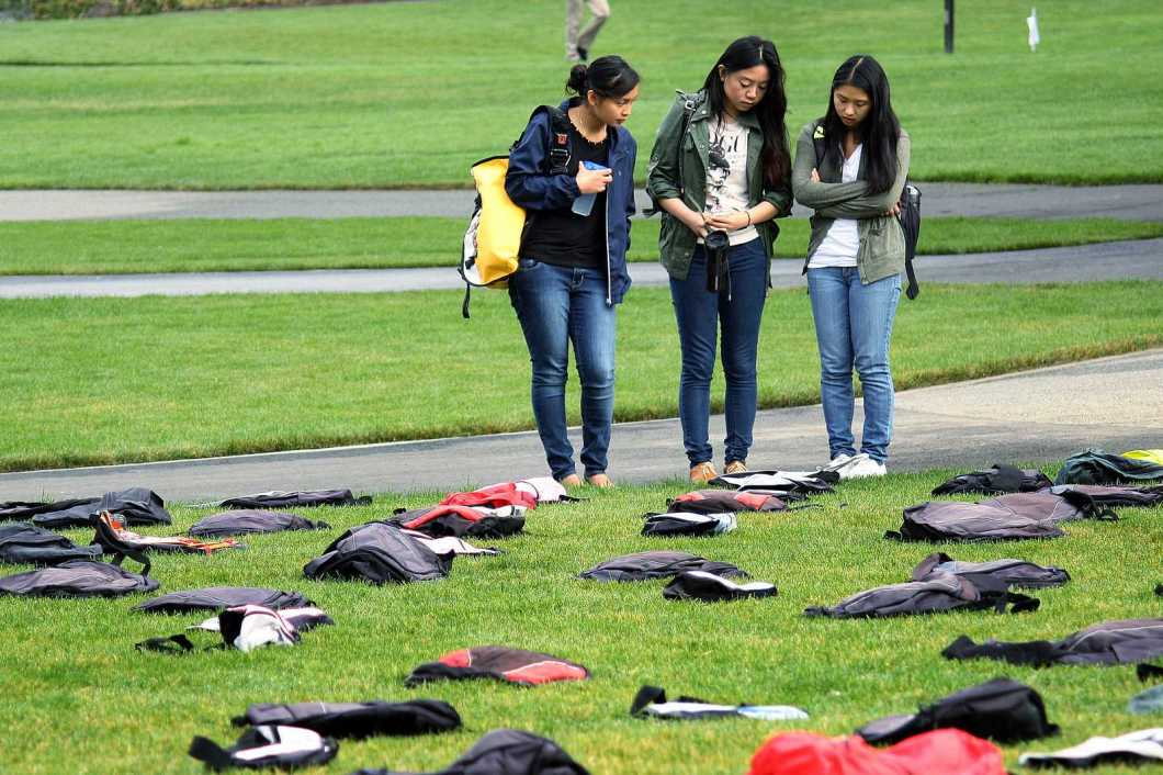 Sophomore nursing students Monique Obiniana (left), Michelle Young (center) and Ashley Chan (right) read a story about one of the 1,100 backpacks placed on the lawn in the Quad which signify the number of students who commit suicide each year. The installation was part of SF State's first suicide prevention conference Friday, Oct. 18, 2013. Photo by Tony Santos / Xpress