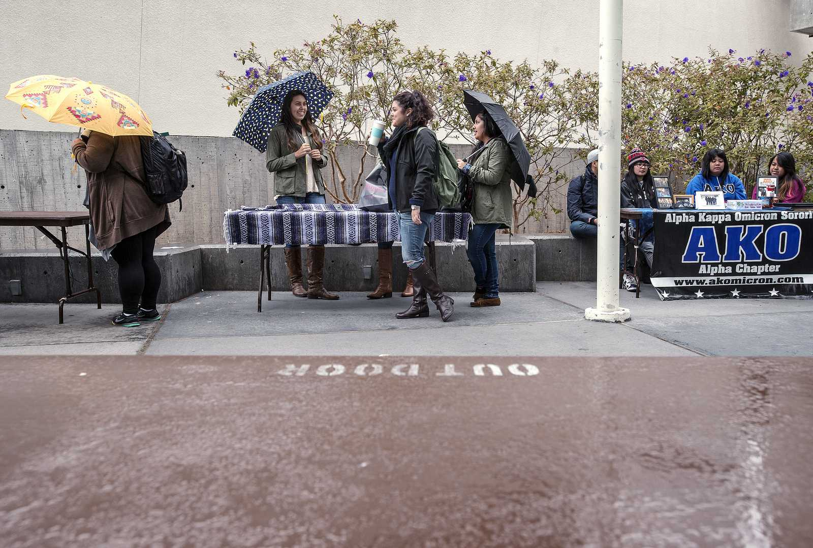 As rain falls down on Malcolm X Plaza, Devoted Women for Change is the last of the organizations to remain tabling. Members Selena Galvez, Karina Rojas, leiloni lund and Alexis Godinez (middle table, left to right) are in the club because they want to set up a Sigma Lambda Gamma chapter at SF State. Photo by Benjamin Kamps / Xpress
