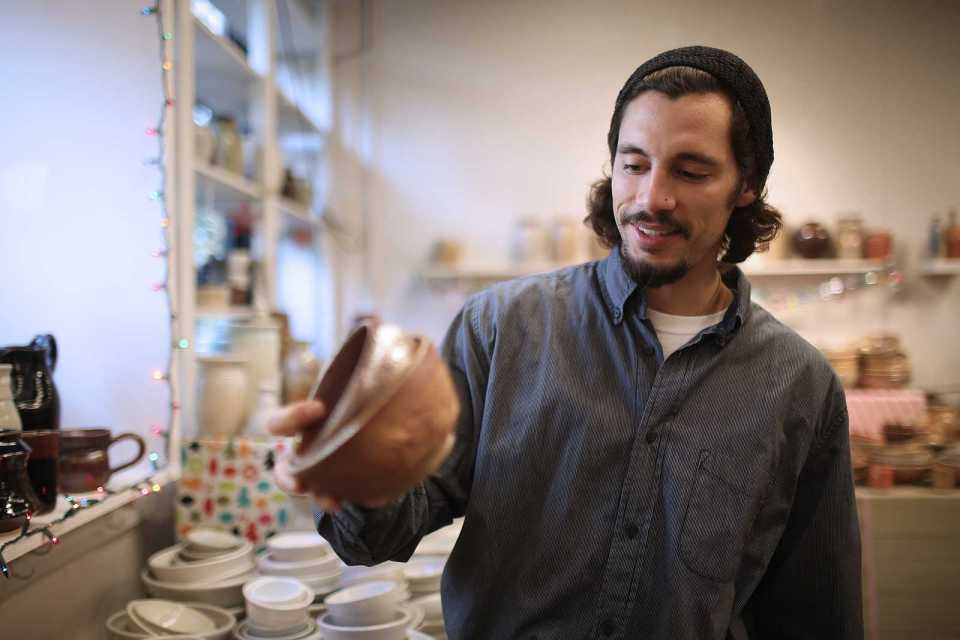 Nick Enfantino looks at bowls that are on display at the Ceramic Guild Annual Holiday Sale on Dec. 2. The sale takes place the entire week of Dec. 2 in FA 192, and all proceeds go towards the ceramic and art programs. Photo by John Ornelas / Xpress