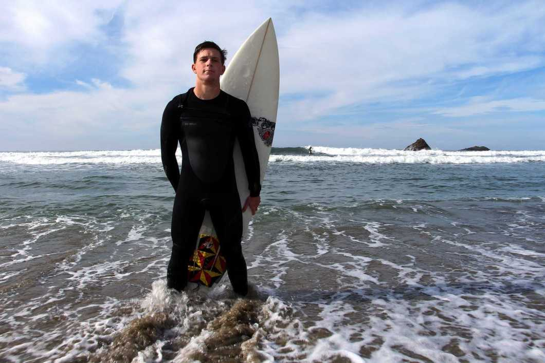 Colin Dwyer, a Psychology major at SF State, stands on the shore of Pacifica State Beach, Monday, Nov. 11, 2013. Dwyer is a professional surfer who will be competing in the Mavericks Invitational, a big wave surf contest in Half Moon Bay, so he trains by surfing at a local beach. Photo by Gavin McIntyre / Xpress