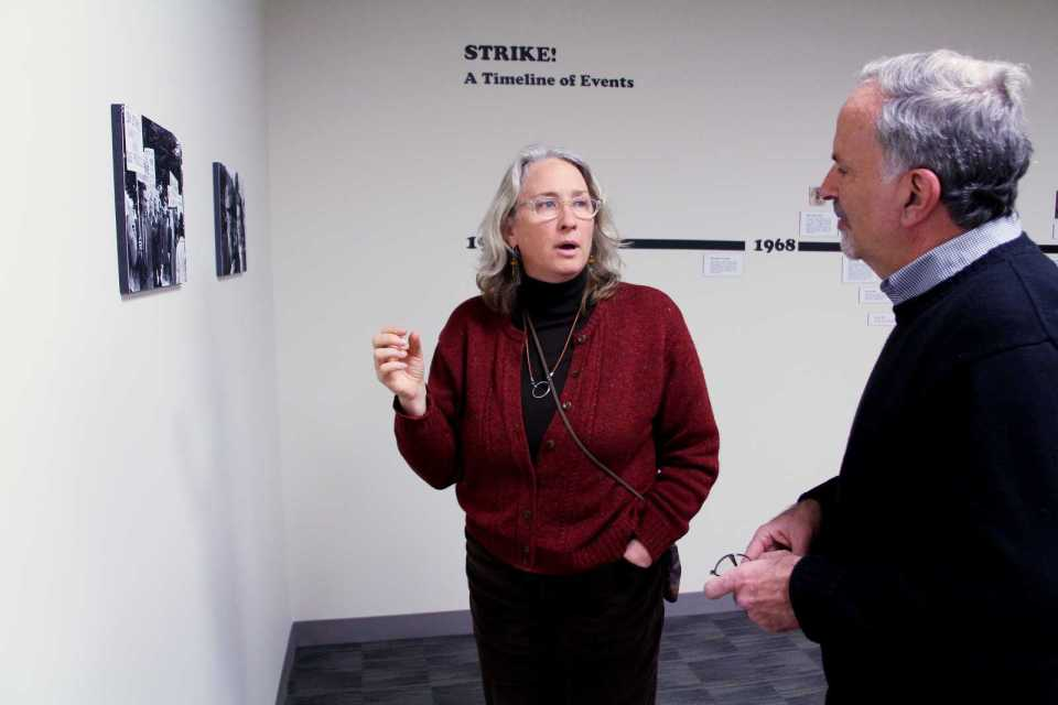 Catherine Powell (left), Director of Labor Archives and Research Center at SF State, talks to Steve Leiken, a History Lecturer at SF State, about the 1968 student strike at SF State, in the Special Collections Section of J. Paul Leonard Library on the 4th floor, Tuesday, Dec. 3rd, 2013. The exhibit features photographs from Phiz Mezey, a former faculty member who was fired after not signing a loyalty oath during the '50s, and came back during the strike to take photos. Photo by Gavin McIntyre / Xpress