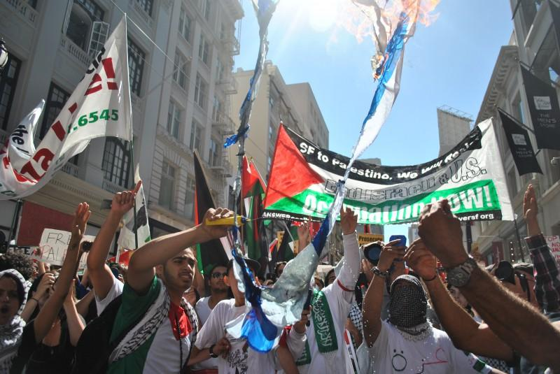 """Free Palestine"" supporters burn Israeli flags on Market Street Saturday, July 26, in San Francisco."