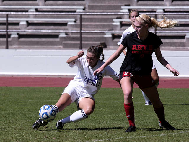 Alex Palomino, left, number 16 of SF State kicks the ball around Maddie Shelton, of the Academy of Art Soccer team at Cox Stadium at SF State, on Sunday, Sept. 7, 2014. SF State won the game 2-1, scoring the game winning goal within 15 minutes left in the game. Daniel Porter / Xpress.