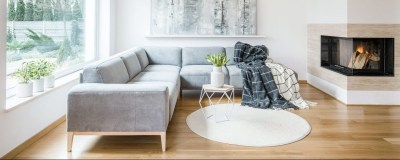 White rug next to a grey corner couch in living room interior with fireplace and painting