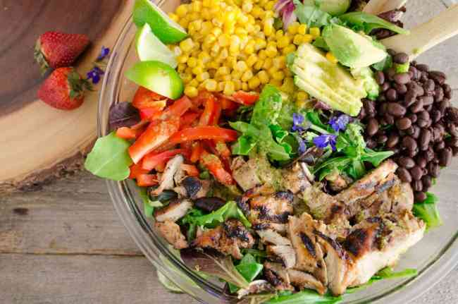 A full view of a Southwestern Grilled Chicken Salad with strawberries and blue flowers for garnish - The Goldilocks Kitchen