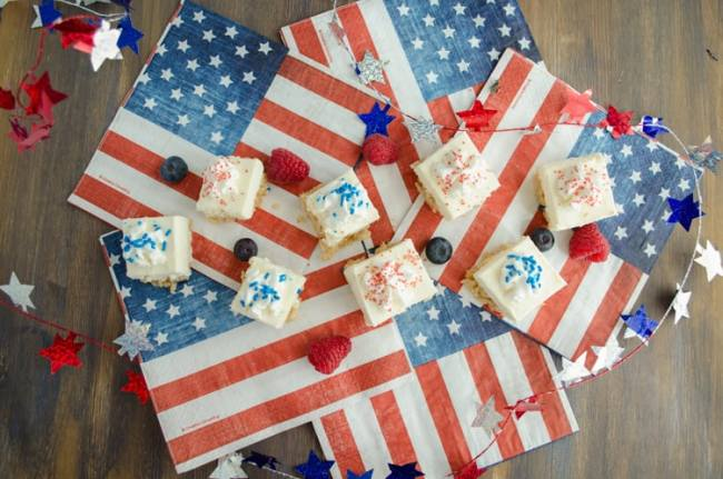 Creamy Crackle Cheesecake bars surrounded by american flags, fresh berries and a garland of stars.