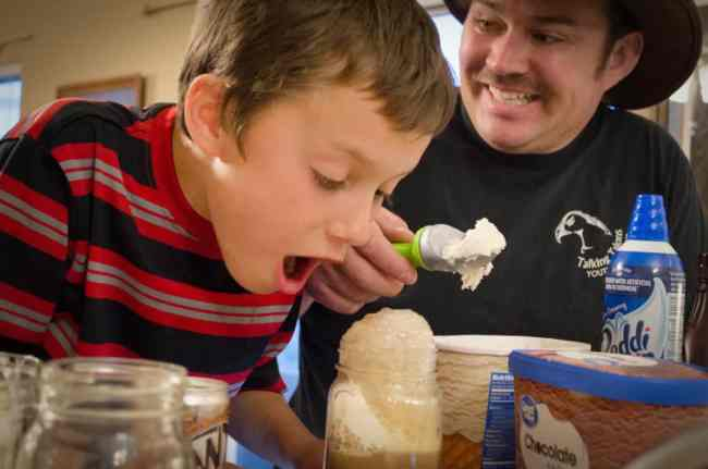 A boy watches his root beer float overflow the rim of his cup -Family Night Root Beer Float Bar