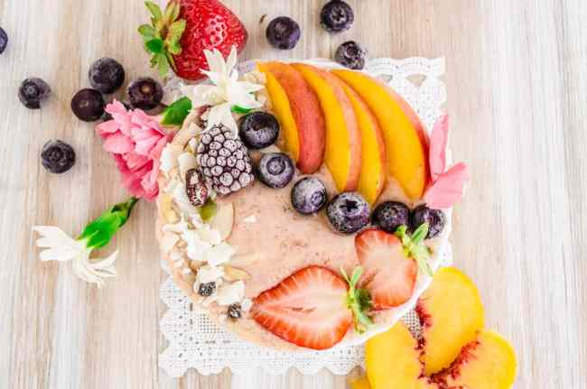 A Strawberry Peach Coconut Smoothie Bowl surrounded by fresh fruit pictured directly overhead.