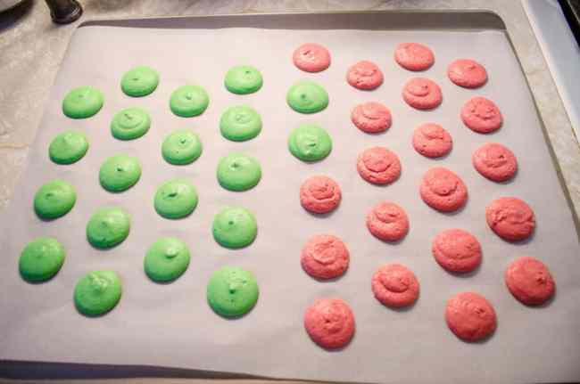 Christmas Macarons piped onto a cookie sheet waiting to be baked.
