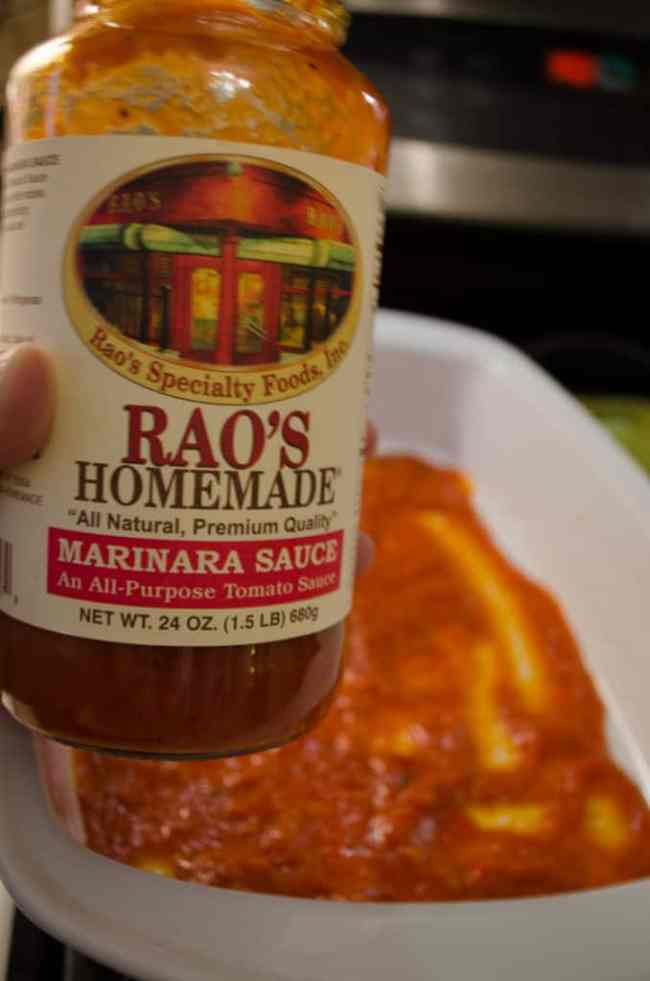 A Jar of RAO's Marinara sauce is displayed with a baking dish containing the sauce in the background.
