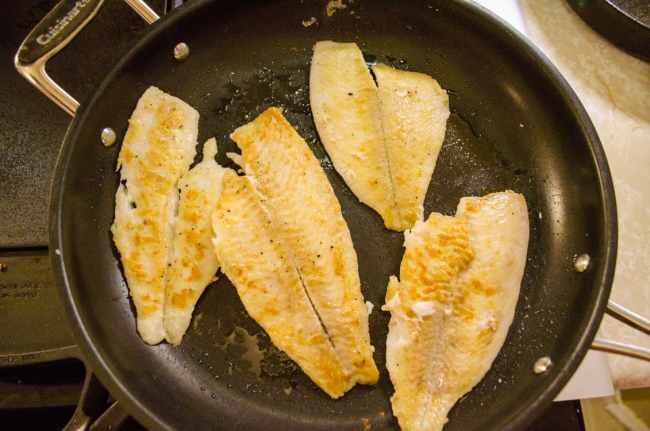 Golden sauteed fish sit in a non-stick pan for Fast Fish Dinner with Herbed Browned Butter.