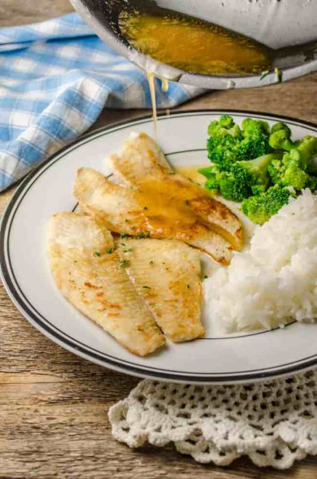 Browned butter and herb sauce being drizzled over Fast Fish Dinner with Herbed Browned Butter sitting on a plate.