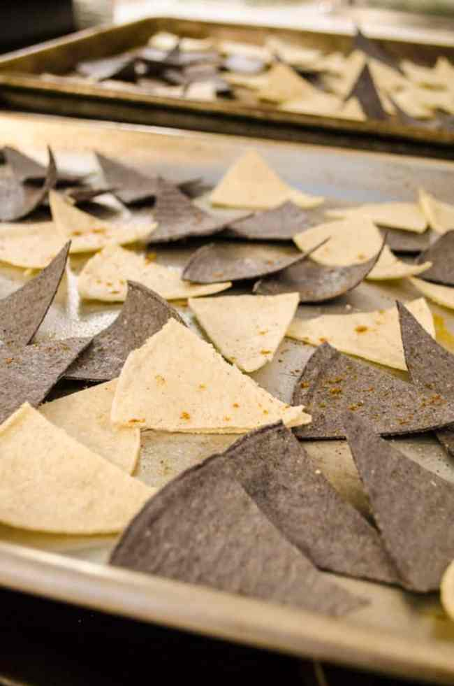 Freshly cut yellow and blue corn tortilla wedges laid out on rimmed baking sheets ready to be baked into Crispy Baked Southwestern Tortilla Chips - The Goldilocks Kitchen