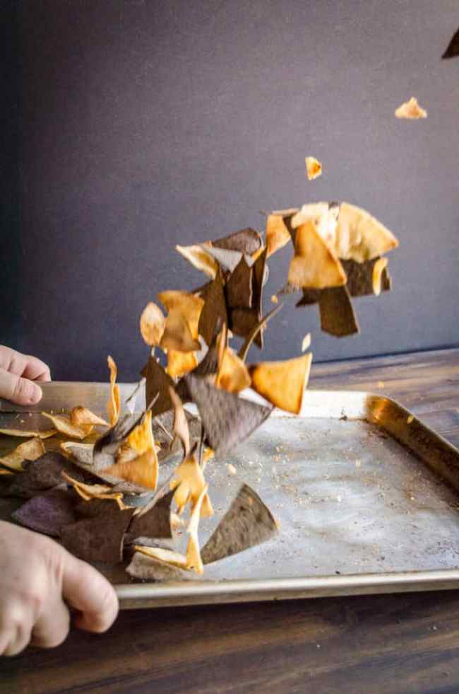 Blue and Yellow Crispy Baked Southwestern Tortilla Chips are tossed into the air off their baking sheet - The Goldilocks Kitchen