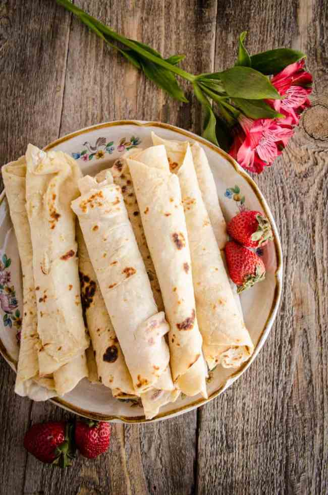 Looking down on a plate full or rolled Norwegian Lefse ready to be eaten - The Goldilocks Kitchen