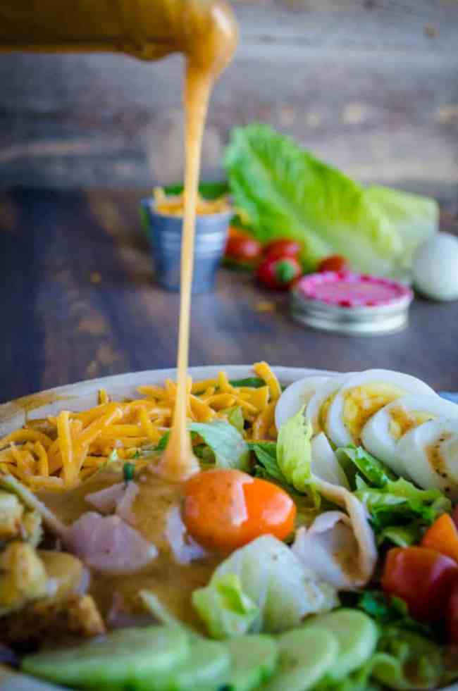 A chef's salad with shredded cheese, sliced egg, cucumbers, tomatoes and romaine lettuce is drizzled with Ten Dollar Dressing. - The Goldilocks Kitchen