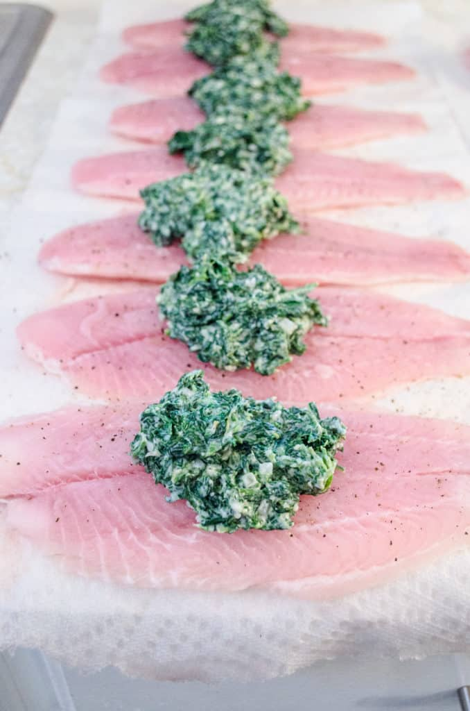 Raw Swai fish fillets are lined up in a row, each topped with a mound of spinach parmesan stuffing for Creamy Stuffed Fish Florentine - The Goldilocks Kitchen