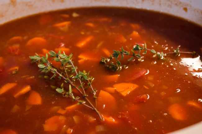 Fresh thyme sprigs placed on top of Slow Cooker Beef and Barley Stew in a slow cooker.
