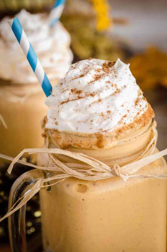 A Frosty Pumpkin Pie Smoothie sits in a glass mason jar mug wrapped with a raffia bow accent, whipped cream and a blue striped straw.