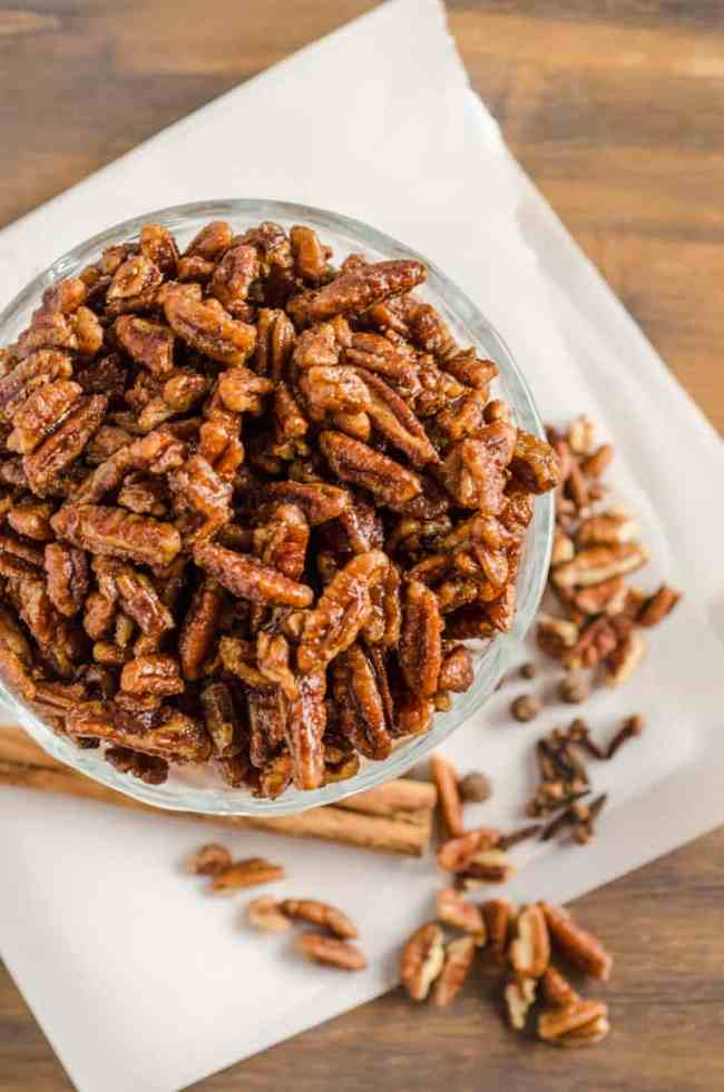 Candied Spice Pecans sit in a glass bowl over parchment paper and a wooden table top - The Goldilocks Kitchen
