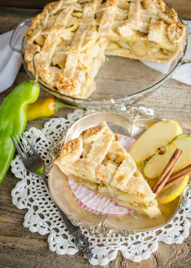 A slice of Green Chile Apple Pie is served up on a silver platter, with the pie and some freshly picked green chiles in the background - The Goldilocks Kitchen