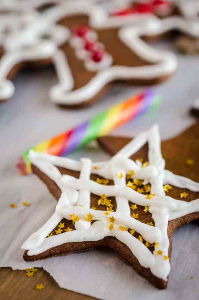 A closeup picture of a Easy Gingerbread Cookies star decorated with white frosting and edible golden glitter stars- The Goldilocks Kitchen