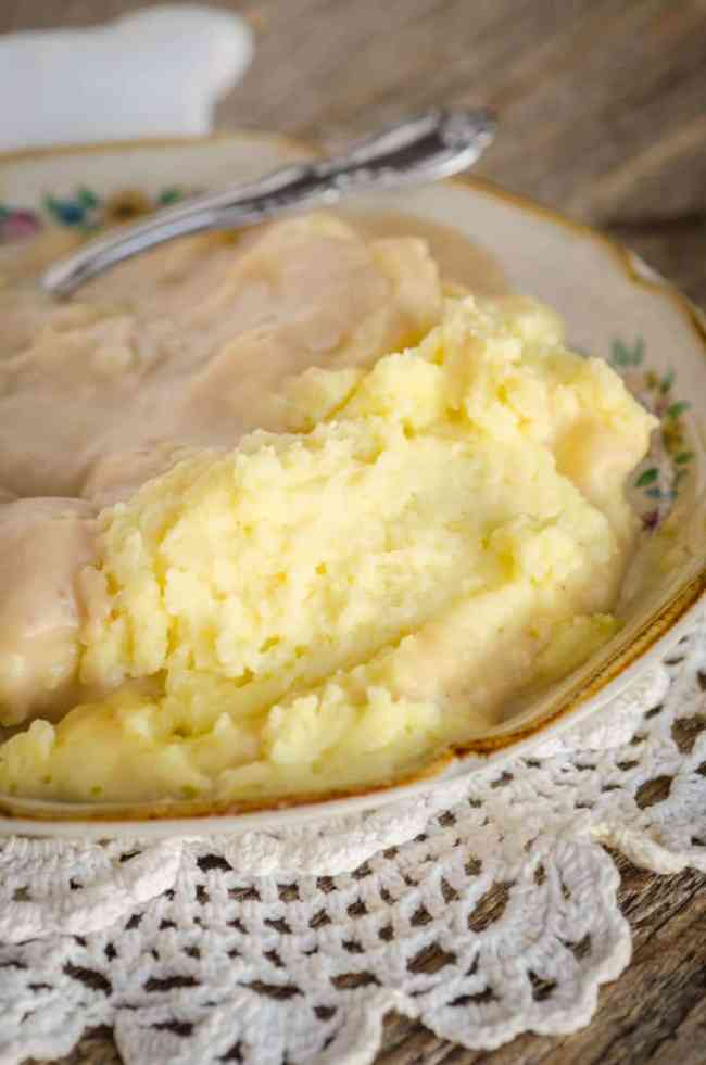 "The Best Mashed Potatoes sit on a plate smothered in turkey gravy for ""How to make turkey gravy"" - The Goldilocks Kitchen"