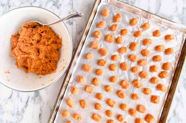 A Baking sheet lined with foil is filled with little Sweet Potato Tater Tots ready to be baked - The Goldilocks Kitchen