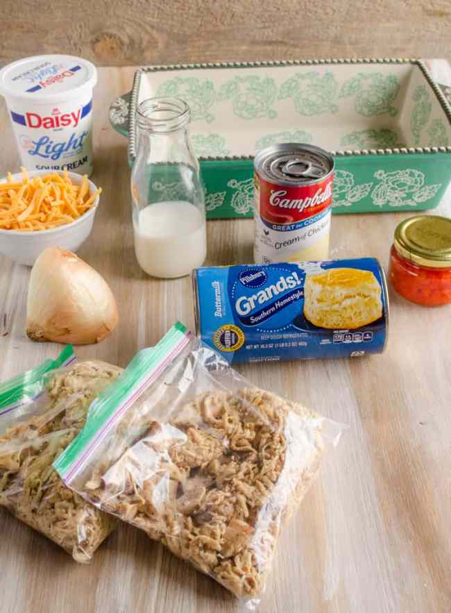 Milk, sour cream, shredded cheddar cheese, half an onion, cream of chicken soup, a green and white casserole dish, a jar of pimiento peppers, and two sandwich baggies filled with shredded cooked chicken are all the ingredients to make a Creamy Chicken Biscuit Bake - The Goldilocks Kitchen