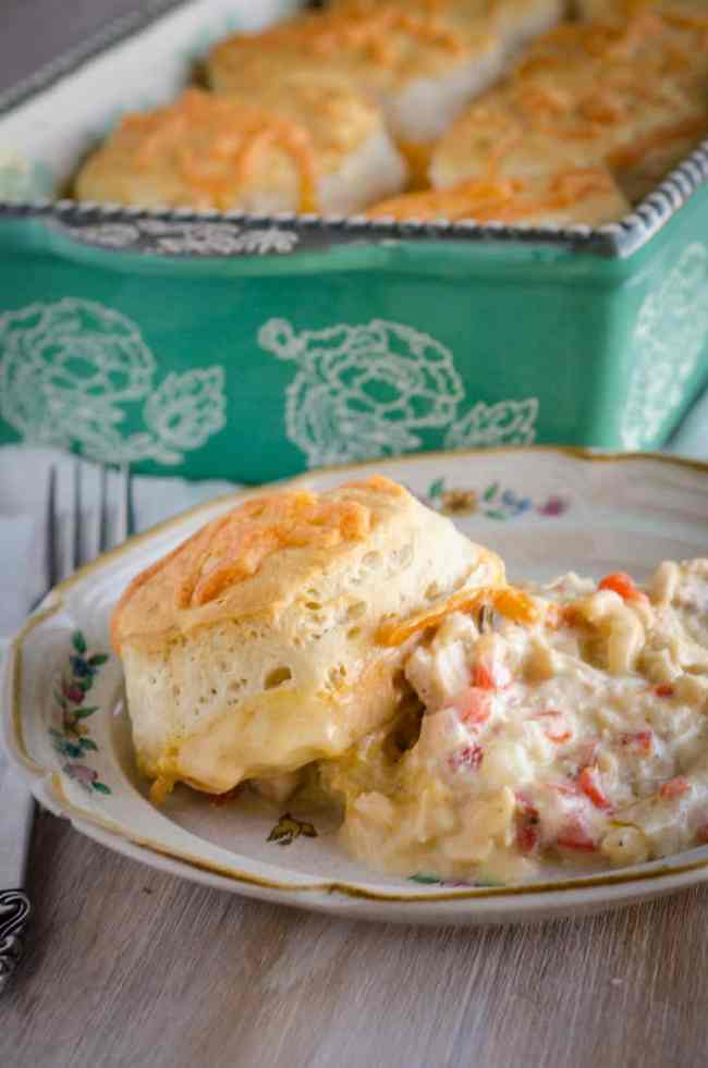 A serving of Creamy Chicken Biscuit Bake sits on a decorative plate showing the creamy chicken and golden baked biscuit on top - The Goldilocks Kitchen